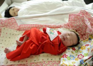 A Chinese mother looks at her newborn baby at a hospital in Shenyang city, northeast China's Liaoning province, March 20, 2014.